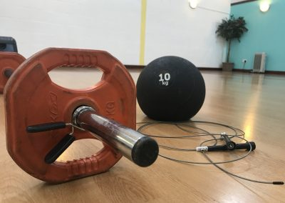 Barbell, weighted ball and skipping rope on the floor of the studio.