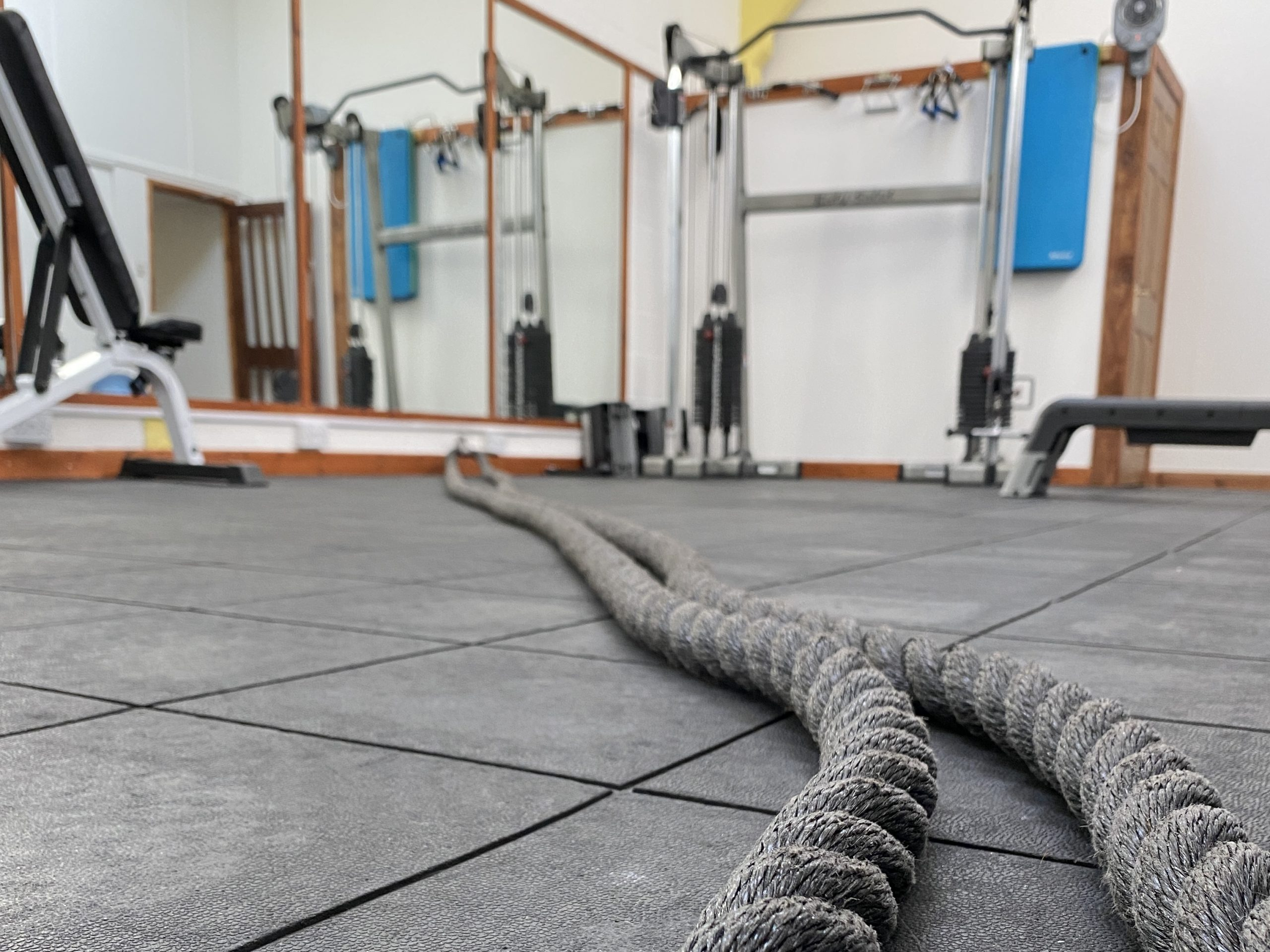Personal training gym with cable machine, battle ropes and bench