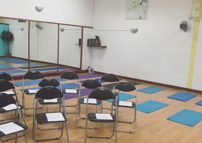 Chairs and mats laid out in the studio ready for a wellness workshop