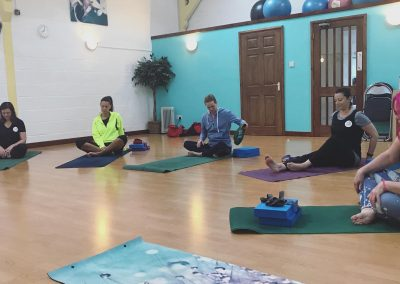 Studio during a yoga class set up with instructor and 6 class attendees