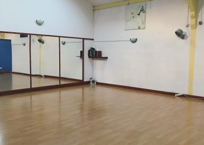 Studio with laminate floor and mirror wall for classes, workshops and courses